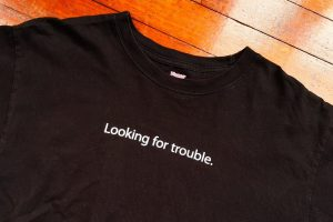 "T Shirt with ""looking for trouble"" slogan"