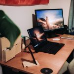black laptop and monitor on brown table